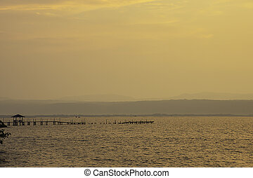 Golden light of sunrise behind the mountains in the sea and the shadow of the wooden bridge at Trat in Thailand.