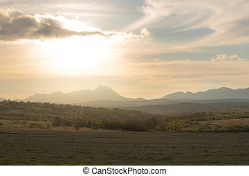 Golden light over fields and mountains