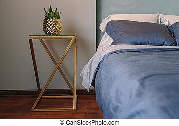 Golden luxury metal bedside table with vase in bedroom with dark blue textile