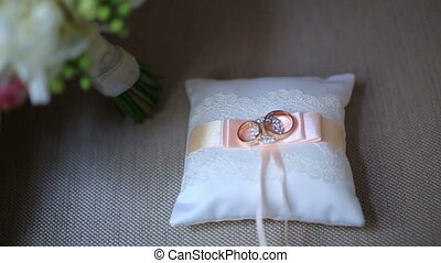 Golden luxury wedding rings on small white cushion with pink ribbon