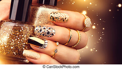 Golden manicure with gems and sparkles. Bottle of...