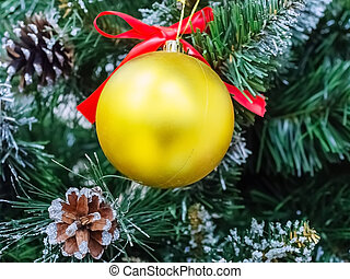 Golden matte christmas ball hanging on artificial pine branch with real cones
