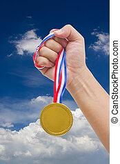 Golden medal in man's hand.