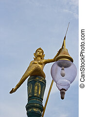 Golden mermaid light poles in the park and blue sky