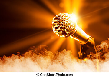 golden microphone on stage with smoke