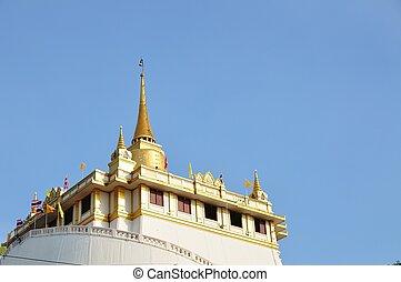 Golden mount of Wat Sakret Temple with blue sky