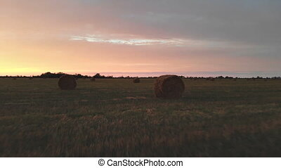 Golden multicolor sunset over a farm field with hay bales....