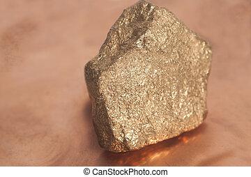 Golden nugget on copper background