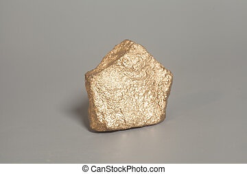 Golden nugget on gray background