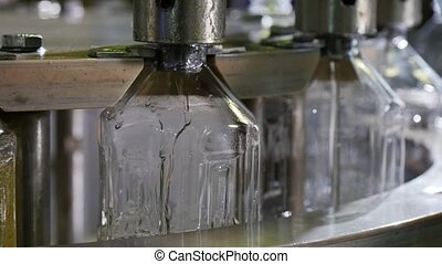 Golden oil splashing in transparent bottles thru metallic...
