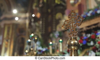 Golden orthodox cross on background of rich decoration of church.