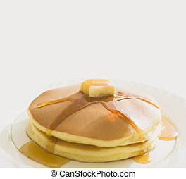 Golden pancakes with butter and warm maple syrup