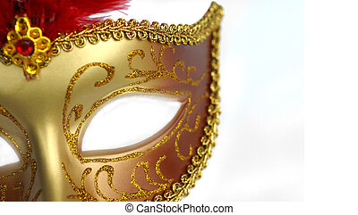 A gold and red masquerade party mask over white background