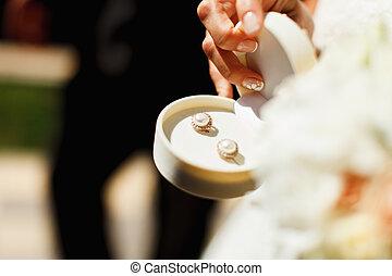 Golden pearl earrings held in a white velvet box