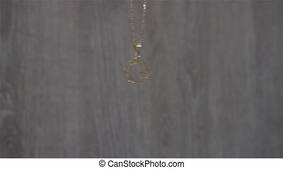 Golden pendant in the shape of a Turkey on a gray...