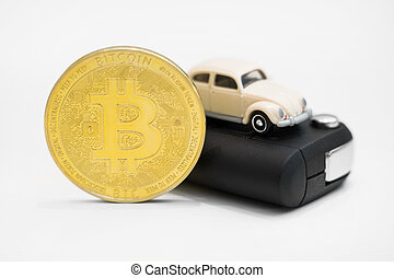Golden physical bitcoin and car key on white background.