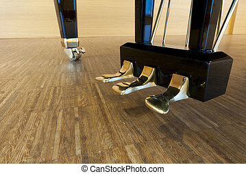 golden piano pedals of a concert grand piano standing on concert stage