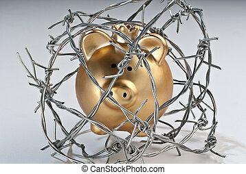 Golden piggy bank behind barbed wire - Golden piggy bank...
