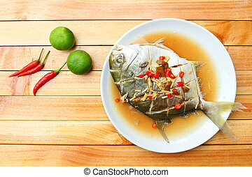 Golden pomfret fish in steamed plum sauce on wooden backgorund