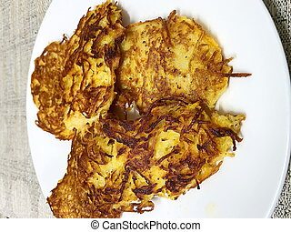 Golden potato fritters or pancakes made from grated potatoes...