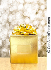 Golden Present box at gold bokeh light background, Leave space for adding your text