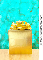 Golden Present box at green bokeh light background, Leave space for adding your text.