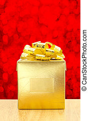 Golden Present box at red bokeh light background, Leave space for adding your text