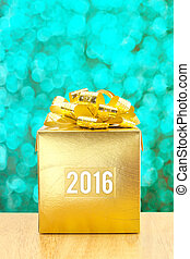 Golden Present box with 2016 word year at green bokeh light background, Leave space for adding your text.
