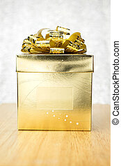 Golden present box with big bow on wooden table at bokeh white blur background, Mock up leave space in middle box to adding your text