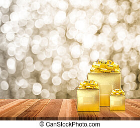 Golden present on wood table top with blur sparkling gold bokeh light background, Gift giving concept, Leave space for adding text for new year or Christmas card.