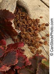 Golden raisins in burlap bag over wooden table