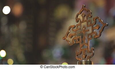 Golden religious cross on background of the lights in...