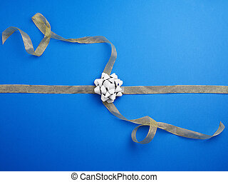 golden ribbon crossed on a dark blue background in the middle of a gray bow