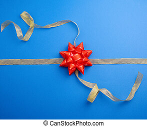 golden ribbon crossed on a dark blue background in the middle of a red bow