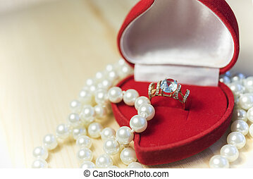 Golden ring with gem and pearls in a red gift box
