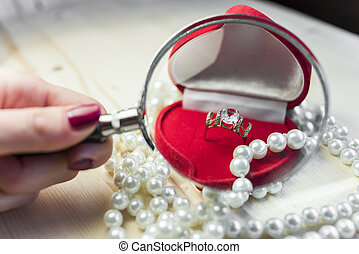 Golden ring with topaz in a red gift box with pearls on the edge of the table