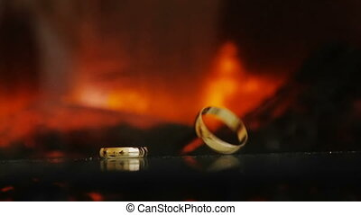 Golden rings on the background of fire from the fireplace Black dark One rolls to the other
