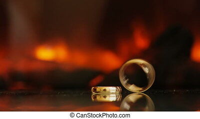 Golden rings on the background of fire from the fireplace. Black, dark. Rotates and turns, spins