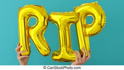 Golden RIP words made of inflatable balloons on blue ...