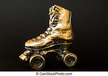 golden roller skate against black background - golden roller...