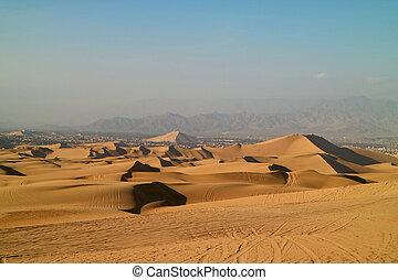 Golden sand dunes with the wheel prints of dune buggies, Huacachina, Ica, Peru