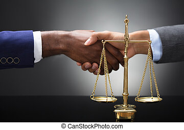 Golden Scale In Front Of Two Businesspeople Shaking Hands
