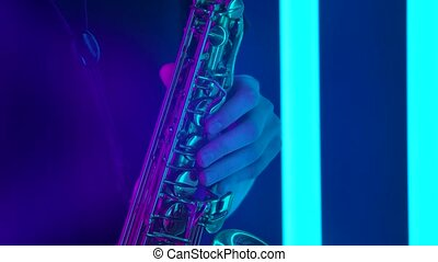 Golden shiny saxophone close up. Detailed footage of male hands touching the keys of a wind instrument against the backdrop of a dark studio with bright neon lights. Slow motion