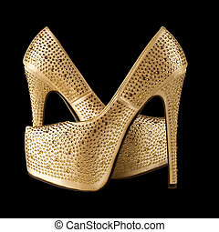 crystals encrusted gold pair of shoes isolated on black. With clipping path