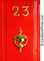 golden sign on red wooden door; 23 and cup; reflection in ...
