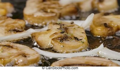 Golden slices of champignons with onion and seasoning are fried into a hot pan with oilin close up. Preparing vegetables for cooking dinner. Delicious mushroom dish. Beautiful wallpaper of cooking for restaurant. Slow motion.