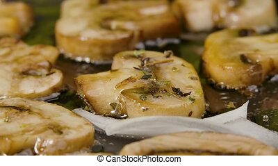 Golden slices of champignons with seasoning are fried into a hot pan with oilin close up. White onion slices are added to fried champignons in pan. Delicious mushroom dish. Beautiful wallpaper of cooking for restaurant. Slow motion.