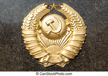 Golden soviet CCCP emblem with hammer and sickle on a marble...