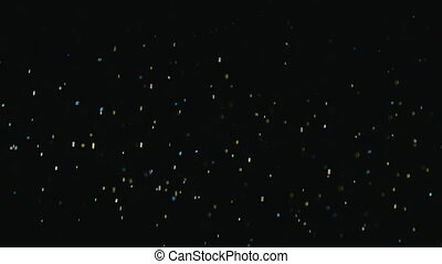 Golden sparkles fall in the form of rain on a black background