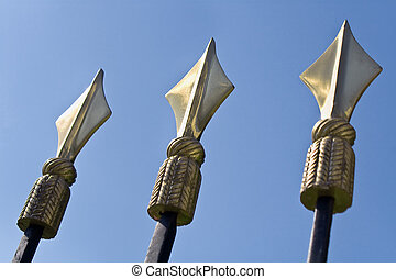 Golden spikes on iron fence over blue sky